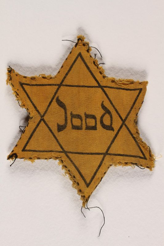 1988.127.3 front Yellow cloth Star of David badge with the word Jood