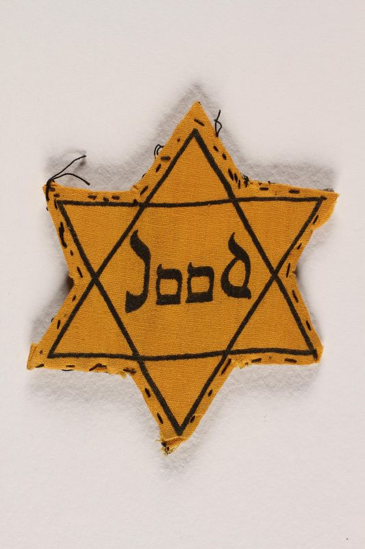 1988.127.4 front Yellow cloth Star of David badge with the word Jood