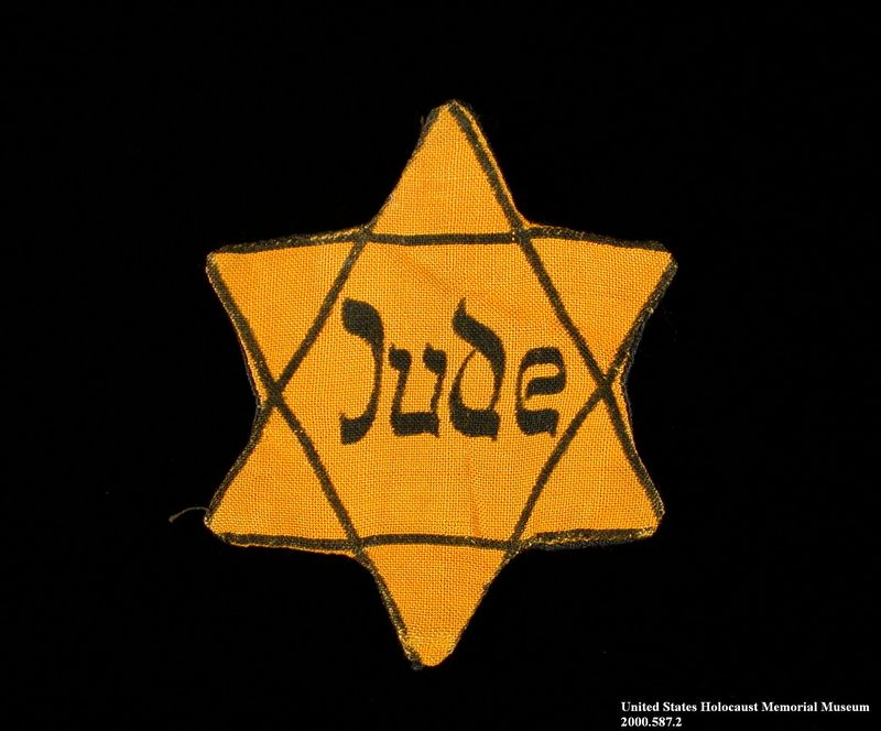 2000.587.2 front Yellow cloth Star of David badge with Jude printed in center