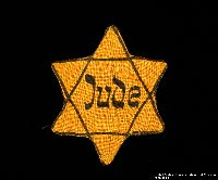2000.587.2 front Yellow cloth Star of David badge with Jude printed in center  Click to enlarge