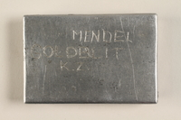 2004.340.2 front Handmade aluminum box incised with the name of a concentration camp inmate found by another inmate  Click to enlarge