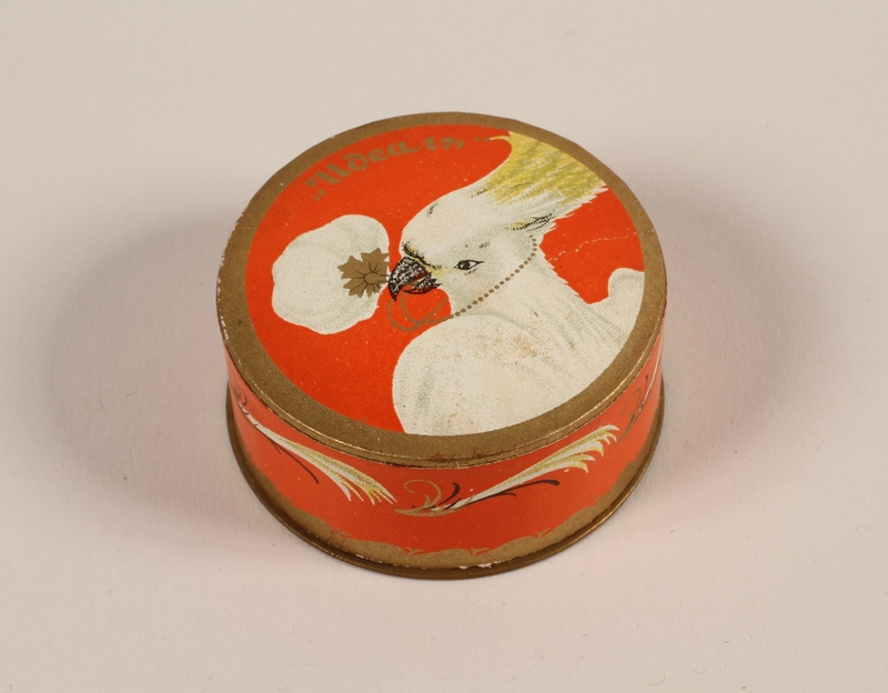 2004.237.1 front Ideal face powder box with a cockatoo design marked Rachel