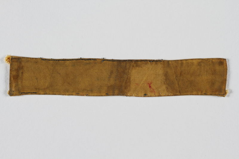 2004.385.3 front Yellow cloth strip sewn to a slave laborer's uniform to identify her as a Jew