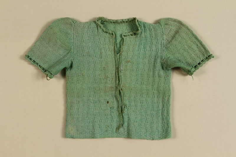 2004.484.1 front Handknit green sweater worn by a young girl while living in hiding in the Lvov sewers