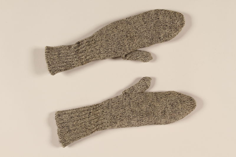 2004.485.16_a-b front Pair of black and white tweed patterned wool knit mittens brought to the US by a German Jewish refugee