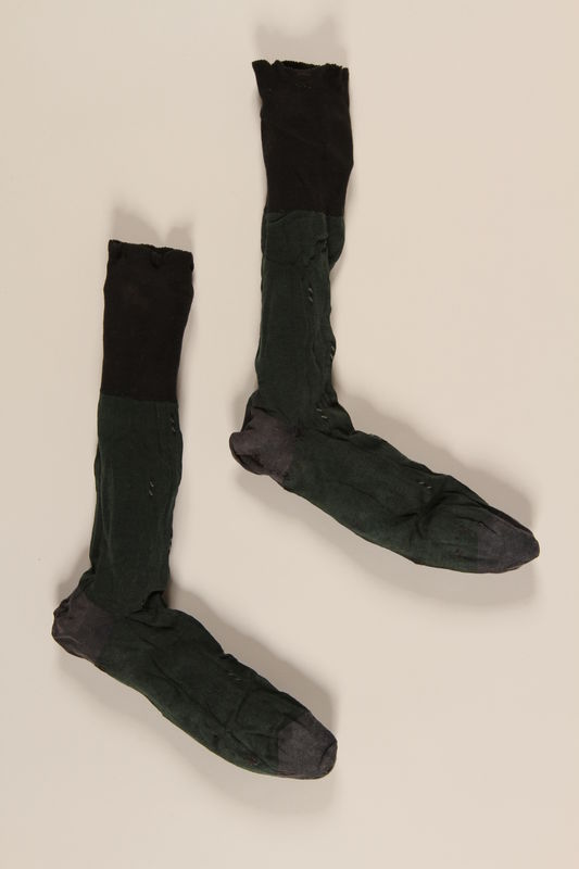 2004.485.19_a-b front Pair of dark green cotton socks brought to the US by a German Jewish refugee