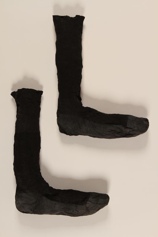 2004.485.21_a-b front Pair of black cotton socks with a gray sole brought to the US by a German Jewish refugee