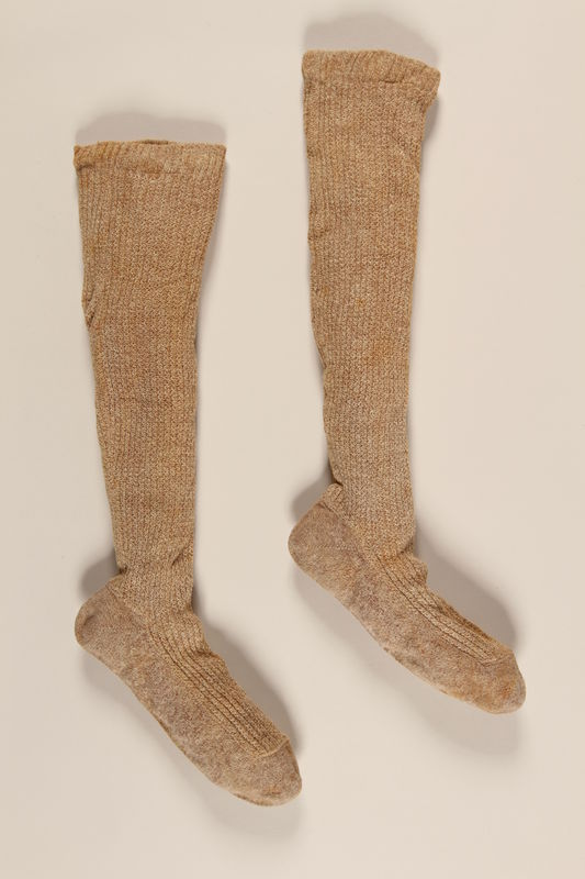 2004.485.22_a-b front Pair of tan and white wool knit knee high socks brought to the US by a German Jewish refugee