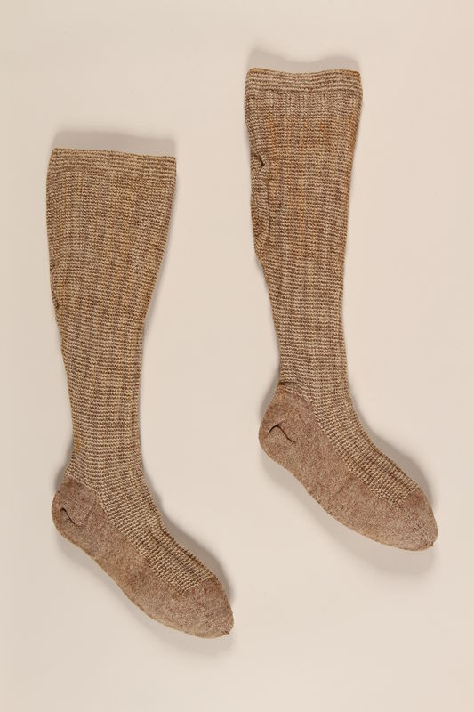 2004.485.23_a-b front Pair of tan and white wool knit tweed patterned knee high socks brought to the US by a German Jewish refugee