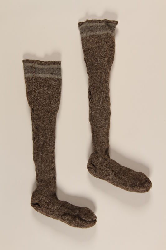 2004.485.24_a-b front Pair of brown and white wool knit kneesocks brought to the US by a German Jewish refugee