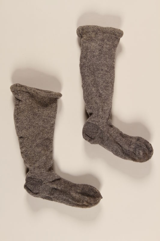 2004.485.25_a-b front Pair of gray and white wool knit socks brought to the US by a German Jewish refugee