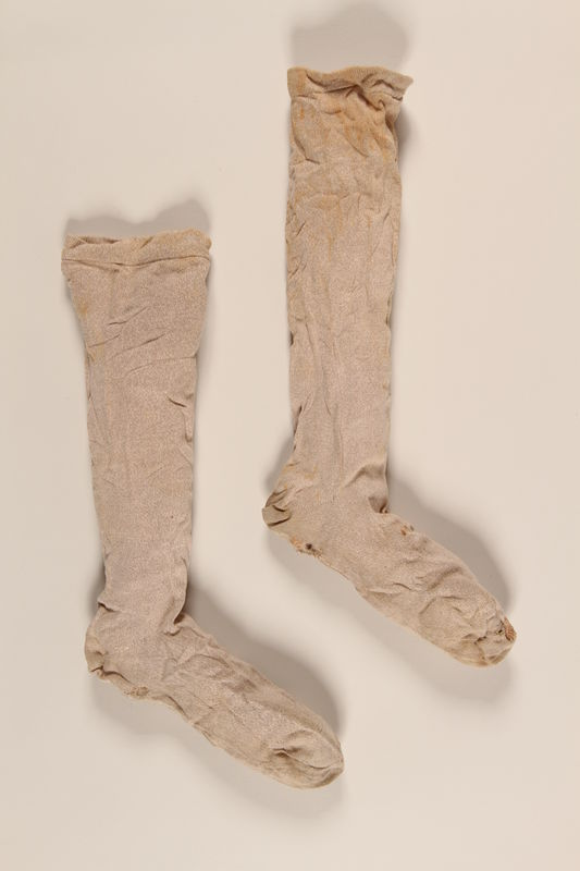 2004.485.26_a-b front Pair of light brown cotton knee high socks brought to the US by a German Jewish refugee