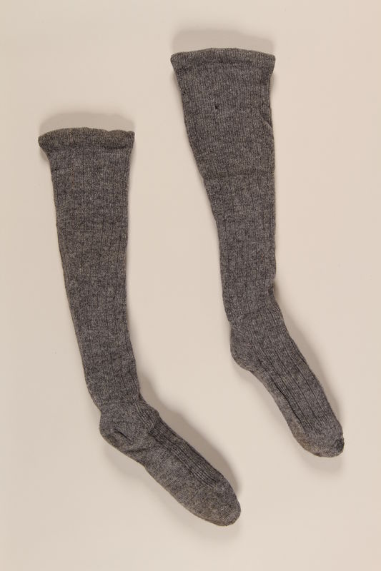 2004.485.27_a-b front Pair of gray wool knit knee high ribbed socks brought to the US by a German Jewish refugee