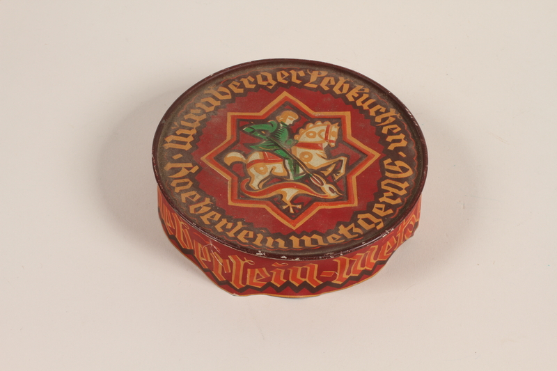 2004.485.48_b front Haeberlein-Metzger almond lebkuchen red lidded tin brought to the US by a German Jewish refugee