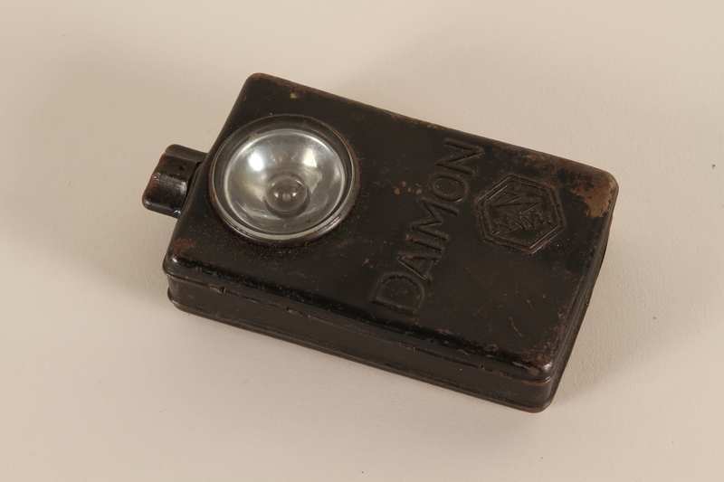 2003.465.5 front Clip-on Daimon battery operated German flashlight acquired by a British officer