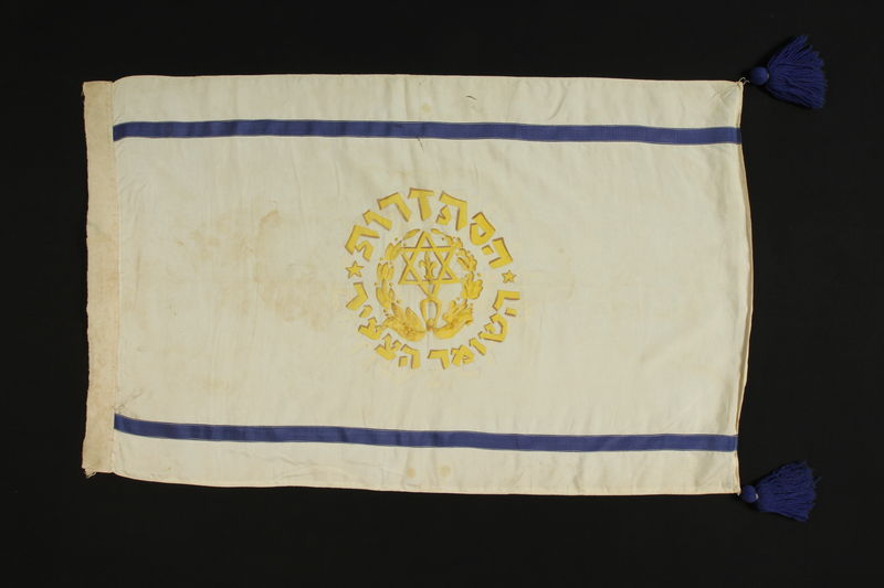 2003.465.9 front Borochov Group white flag with 2 blue stripes, yellow Star of David and fleur-de-lis acquired by a British officer