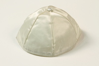 2004.524.11 front White satin yarmulke with a button owned by a German Jewish refugee  Click to enlarge