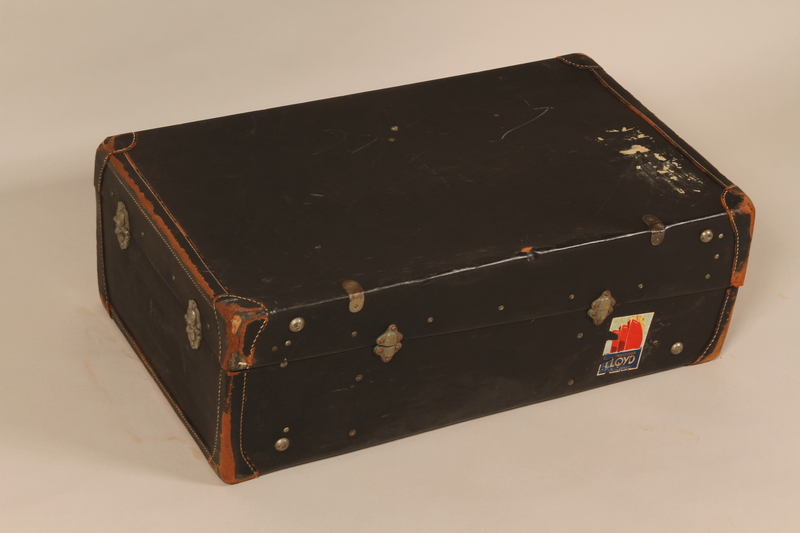2004.526.2 back Black flat top steamer trunk used by a Jewish Austrian refugee