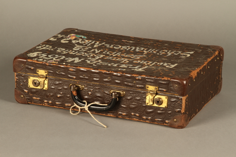 2005.89.1 3/4 view Faux alligator suitcase issued to inmates released in Bergen-Belsen prisoner exchange