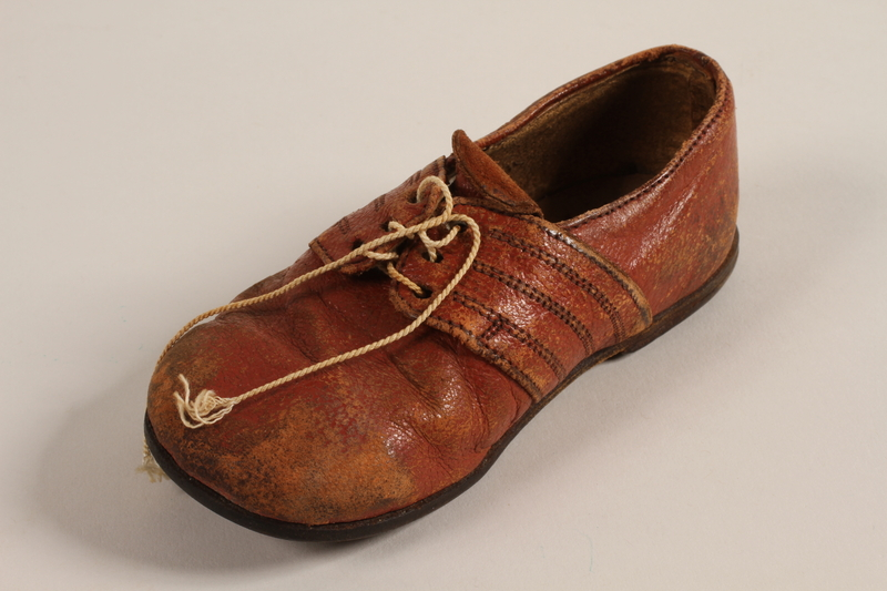 1998.41.1 front Toddler's red leather shoe worn by a Jewish refugee from German occupied France