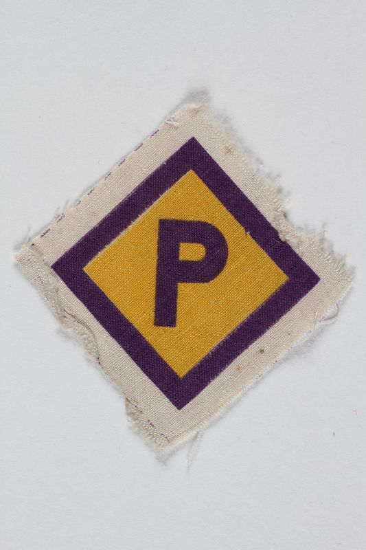 2005.83.12.2 front Forced labor badge, yellow with a purple P, to identify a Polish forced laborer