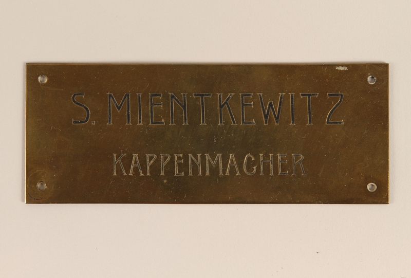 2004.704.4 front Small brass sign from the family capmaking business brought to the US by a Jewish refugee from Vienna