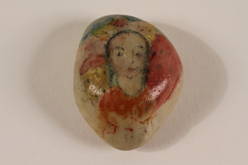 2004.705.10 front Small rock with a painted portrait of a dark haired woman killed in a concentration camp