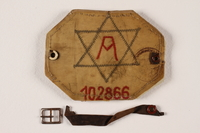 2004.706.2 front Plastic covered Arbeitsjude [Jewish worker] armband, number 102866 worn in the Boryslaw ghetto  Click to enlarge
