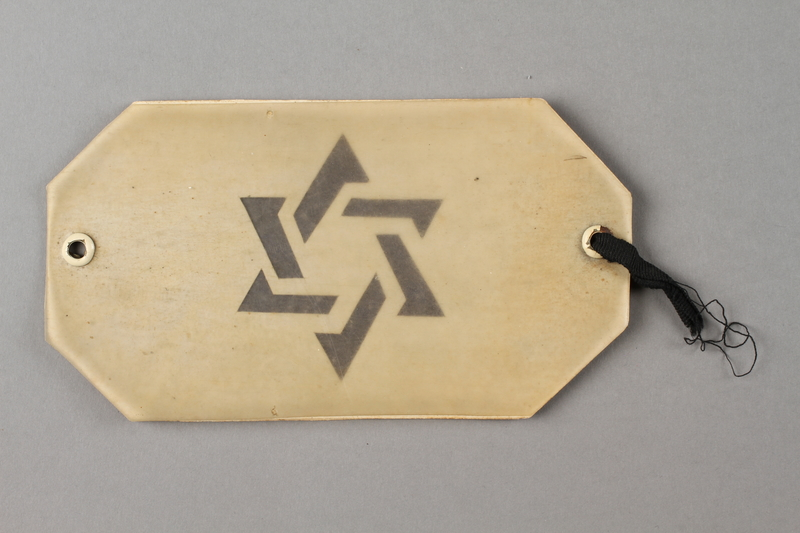 2004.706.4 front Plastic covered paper armband with a cut out Star of David worn in the Boryslaw ghetto