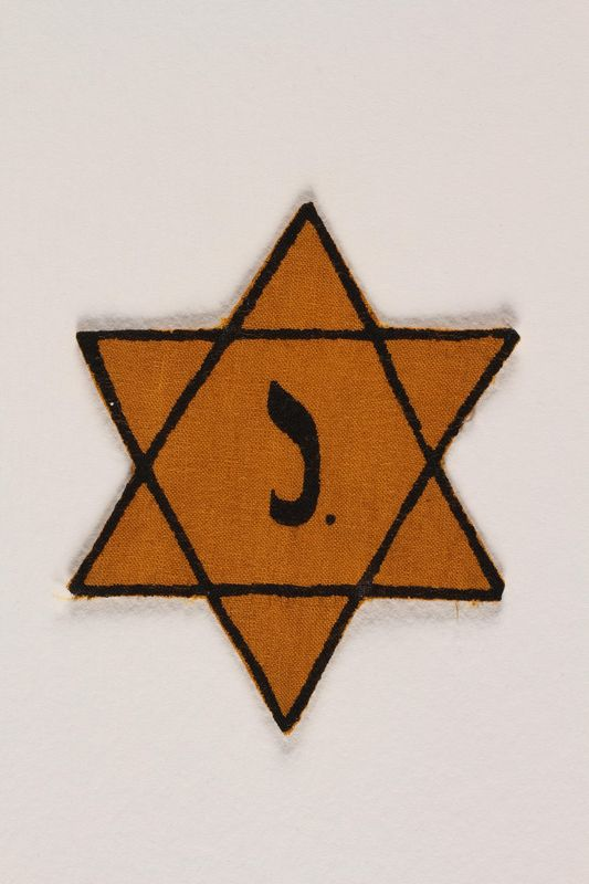 2003.318.3 front Star of David badge with letter J owned by Jewish Belgian couple