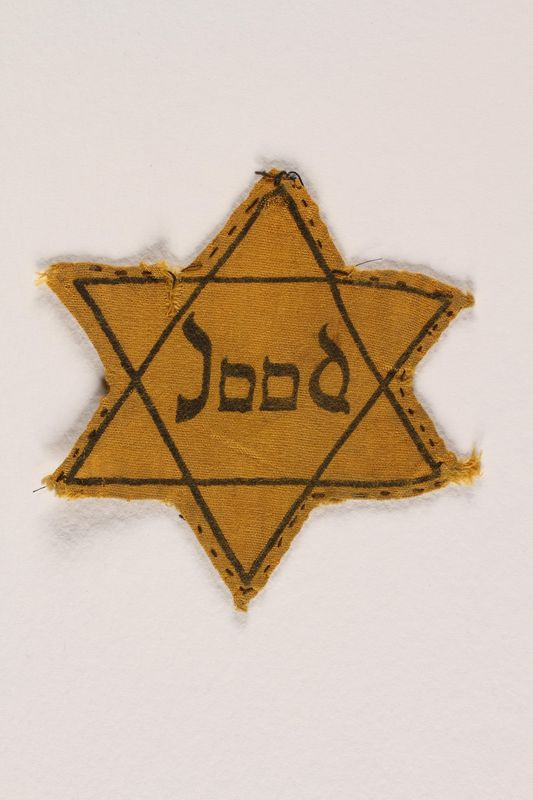 2005.175.3 front Yellow cloth Star of David badge printed with Jood, Dutch for Jew, worn by a German Jewish refugee