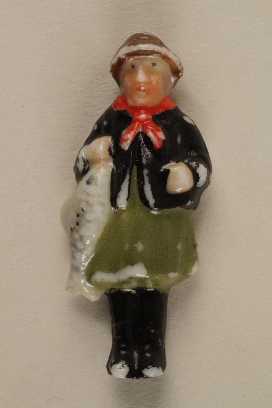 2005.367.18 front Miniature figurine in Bavarian dress with a fish for charity campaign donors