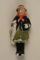 2005.367.18 front Miniature figurine in Bavarian dress with a fish for charity campaign donors  Click to enlarge