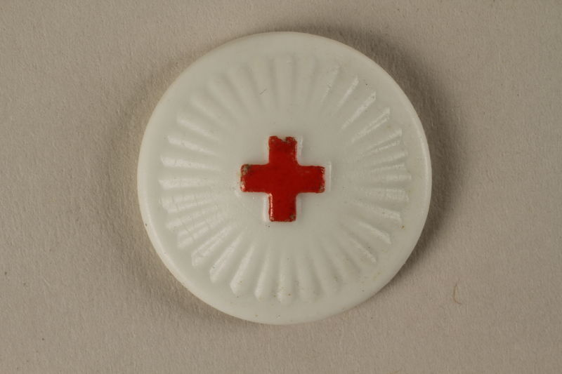 2005.367.24 front White pin with a red cross