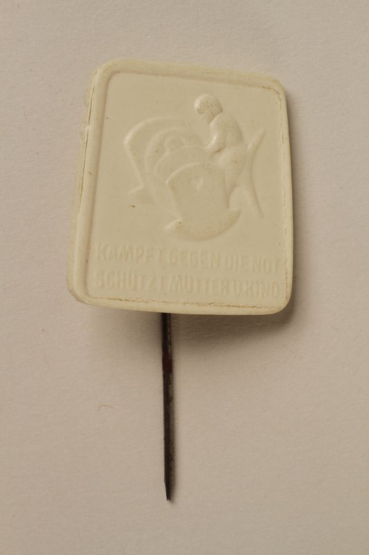 2005.367.25 front White plastic pin with a mother and baby for a Nazi Party charity drive