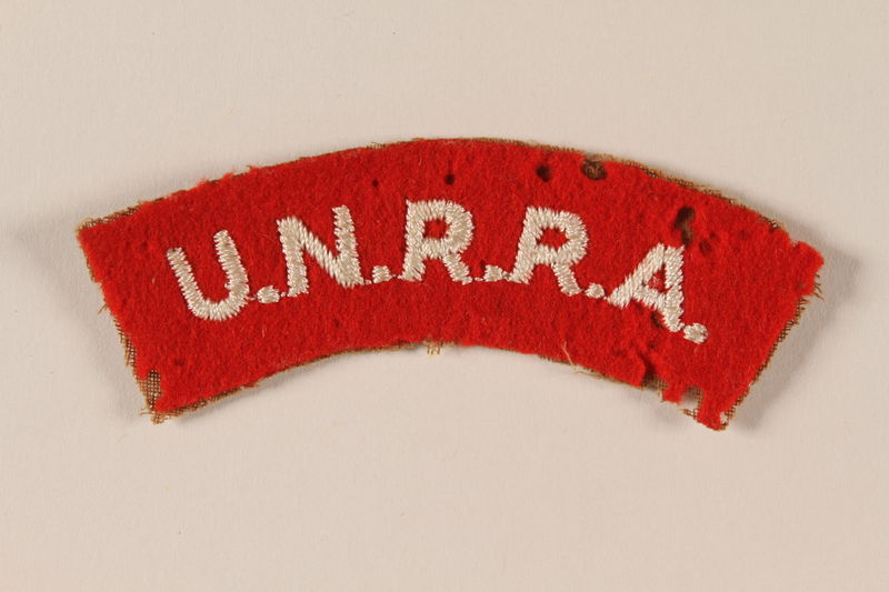 2005.379.2 front UNRRA red felt patch with acronym worn by a refugee aid worker