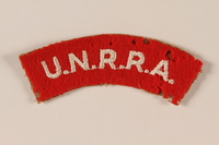 2005.379.2 front UNRRA red felt patch with acronym worn by a refugee aid worker  Click to enlarge