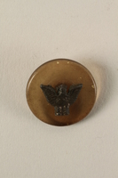 2005.416.14 front Plastic button with metal eagle owned by a US soldier  Click to enlarge