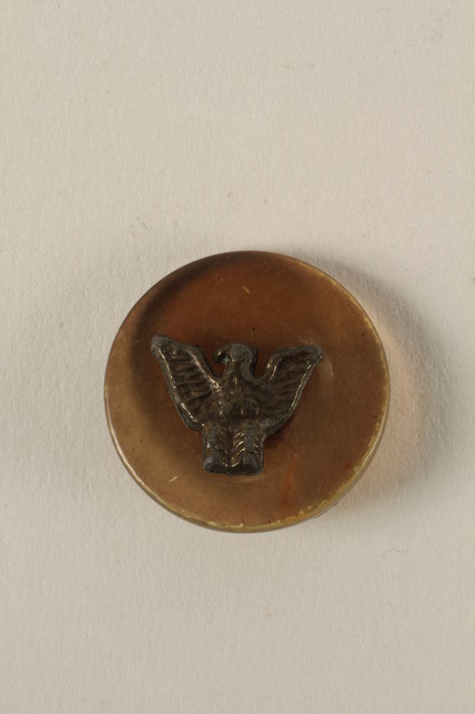 2005.416.15 front Plastic button with metal eagle owned by a US soldier