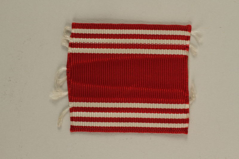 2005.416.20 front US Army soldier's red and white striped ribbon