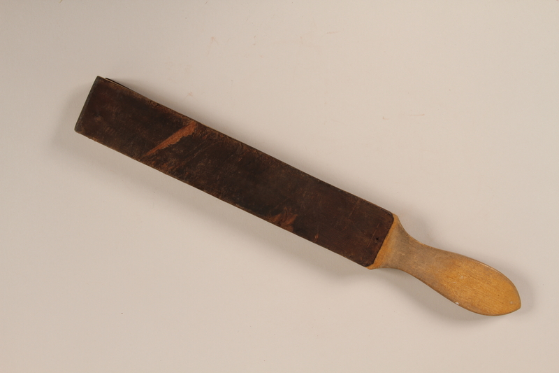 2005.457.26 front Wood mounted razor strop used by a barber in a concentration camp