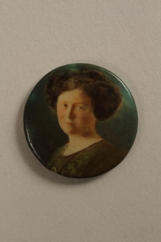 2006.19.8 front Button with a portrait of young woman with dark hair