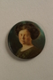 Button with a portrait of young woman with dark hair