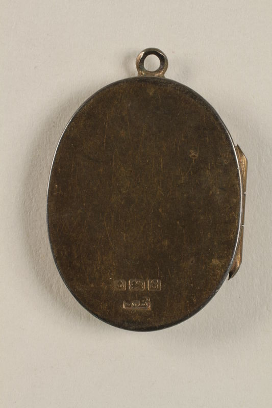 2006.19.23 back closed Oval locket with 2 photos of a young woman owned by emigres in Shanghai
