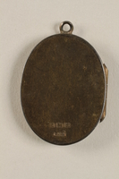 2006.19.23 back closed Oval locket with 2 photos of a young woman owned by emigres in Shanghai  Click to enlarge