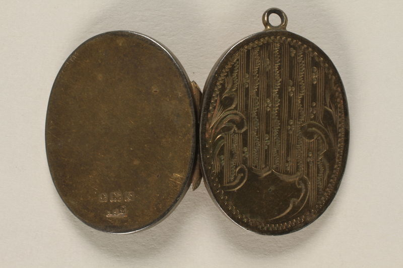 2006.19.23 back open Oval locket with 2 photos of a young woman owned by emigres in Shanghai