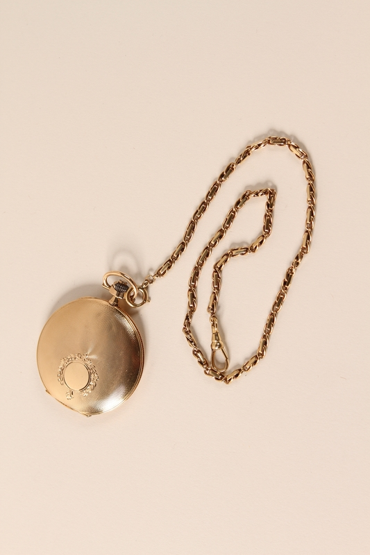 2006.450.1 closed Pocket watch with chain traded for food by a concentration camp inmate and recovered postwar