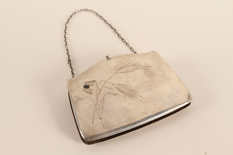 2007.42.1 front Silver purse with an engraved butterfly and a chain strap used by a hidden child