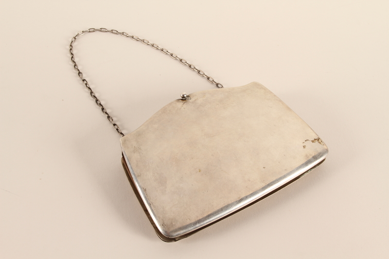 2007.42.1 back Silver purse with an engraved butterfly and a chain strap used by a hidden child