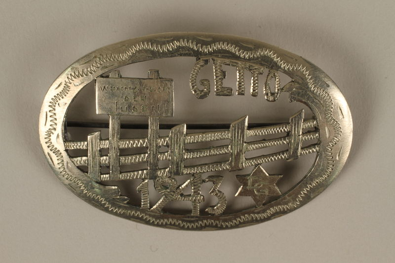 2007.45.2 front Brooch with a cut-out design of the fence and Jewish quarters sign made in Łódź Ghetto